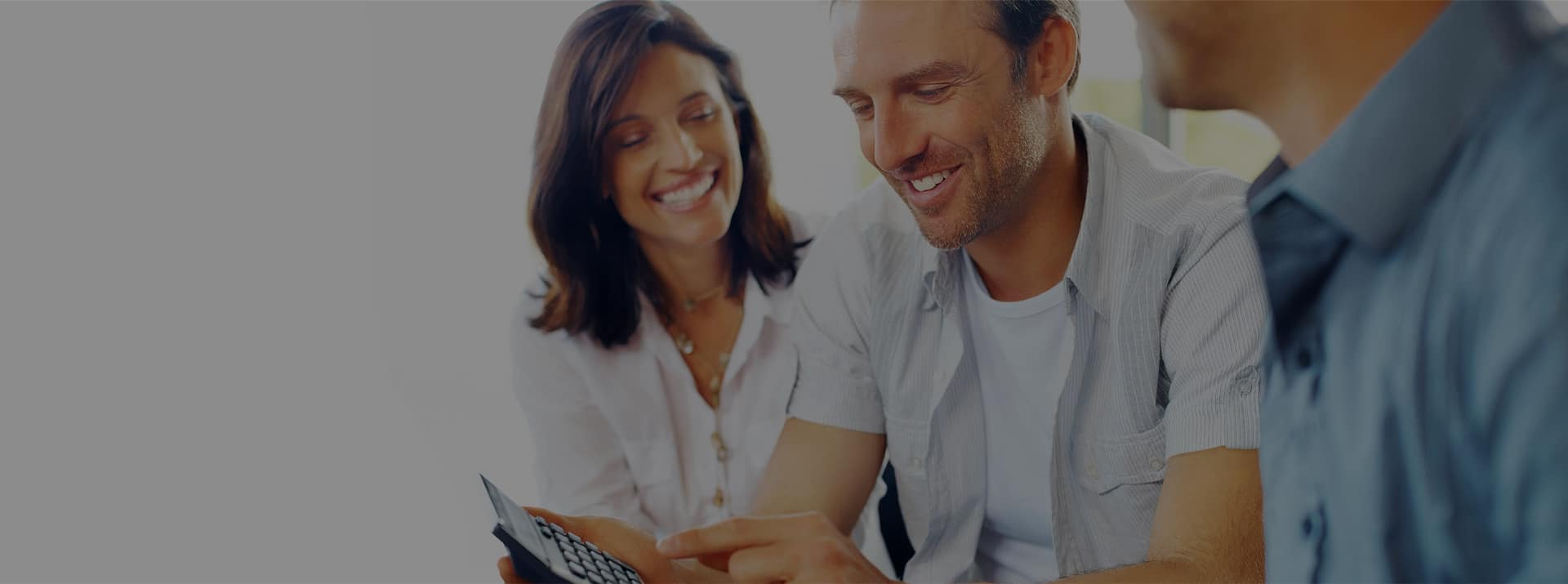 smiling couple looking at calculator